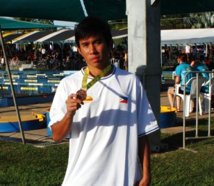 Allan Jovero holds one his three bronze medals won during the first day of swimming competitions in the 2009 Arafura Games at the Casuarina Swimming Center in Darwin, Australia.