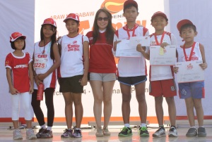 Phoenix Petroleum Brand and Marketing Manager Celina Matias awards the winners of the 3K category of the Phoenix Family Fun Run on March 9 at SM Lanang Premier.(pr photo)