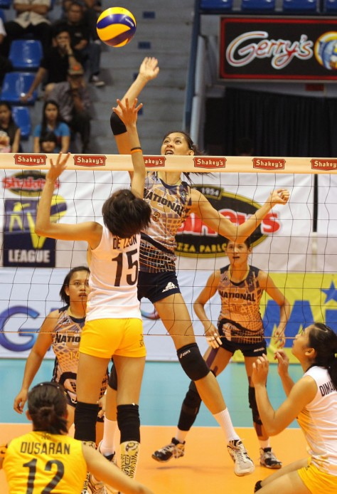 NU's Jaja Santiago towers over UST Jessey de Leon as she smashes a hit during Game Two of their Shakey's V-League Final Four duel at The Arena in San Juan.(pr photo)